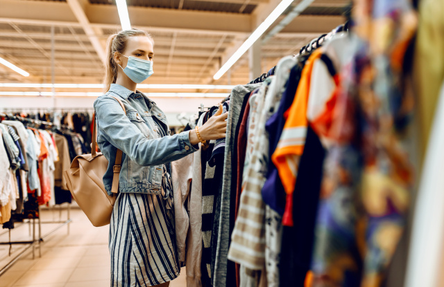 girl in a medical protective mask on her face, chooses new clothes in the store and smiles. Shopping, quarantine, coronavirus